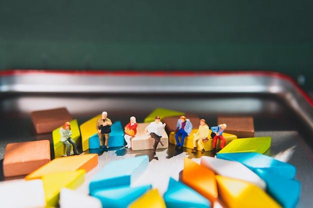 Miniaturmenschen, die auf tangram-puzzle sitzen, das als geschäftliches und soziales konzept verwendet