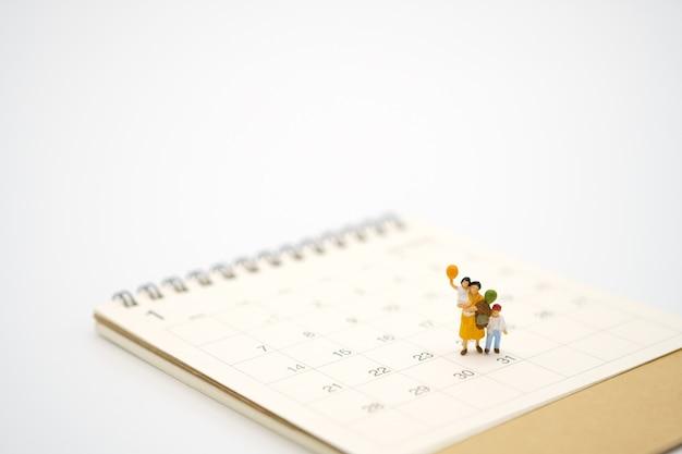 Miniaturmenschen, die auf weißem kalender stehen