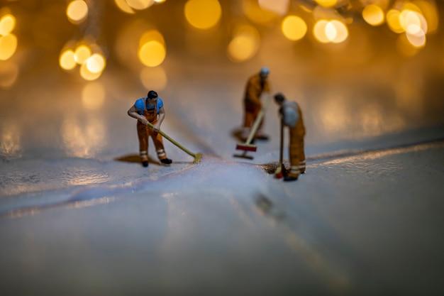 Miniaturmenschen, die fliesenboden mit unschärfehintergrund reinigen.