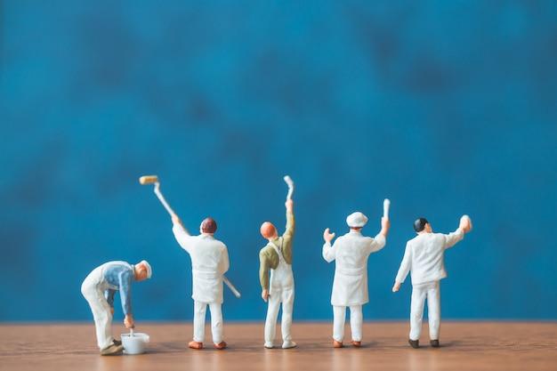 Miniaturmenschen, die pinsel vor einem blauen wandhintergrund halten