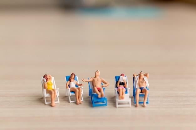 Miniaturmenschen, die sich am strand sonnen, sommerzeitkonzept