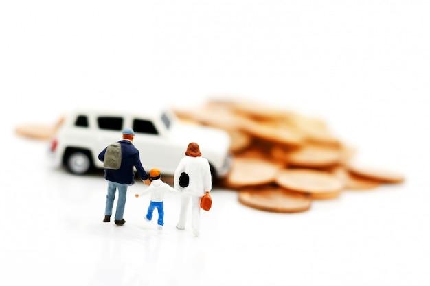 Miniaturmenschen: eltern und kinder gehen mit münzen zum automodell. konzept von geld, finanzen und autokredit.