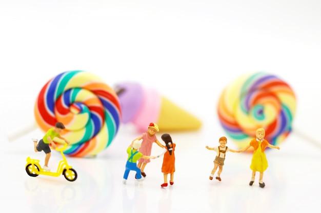 Miniaturmenschen: familie und kinder vergnügen sich mit regenbogen.