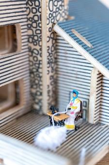 Miniaturmenschen frau, die an einer nähmaschine an ihrem haus näht. näherinnen arbeiten an der nähmaschine