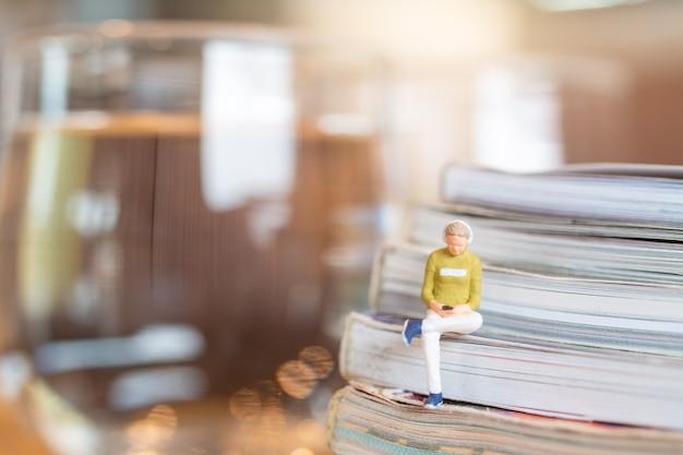 Miniaturmenschen frau, die kopfhörer trägt und musik auf smartphone hört