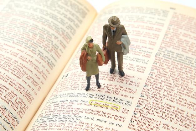 Miniaturmenschen. frau und mann stehen auf dem bibeltext. suche nach dem weg des lebens. ich bin der weg.
