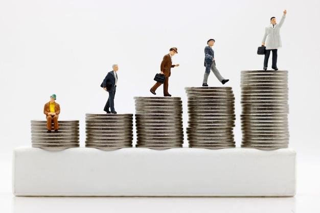 Miniaturmenschen: geschäftsleute, die an die spitze des münzgeldes gehen. konzept des weges zu zweck und erfolg, finanziell und geld.