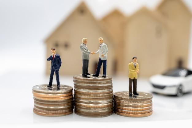 Miniaturmenschen: geschäftsleute, die sich die hände auf münzen schütteln, stapeln sich mit haus und auto. konzept der investition in wohnraum und fahrzeuge.