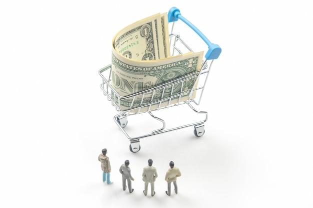 Miniaturmenschen. geschäftsleute stehen in der nähe eines einkaufskorbs mit dollars. geschäft mit konsumgütern. industrieindustrie konzept