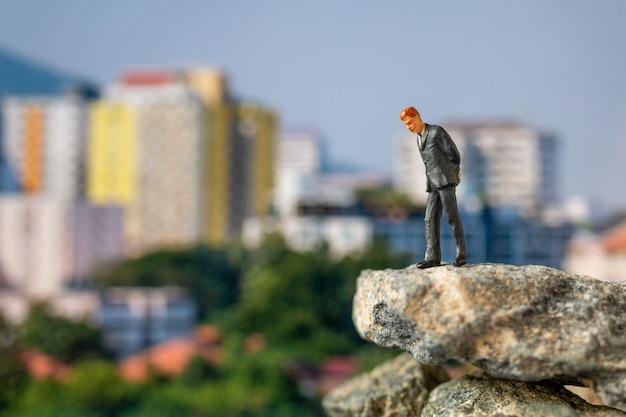 Miniaturmenschen, geschäftsmann, der auf dem felsen mit dem gebäude steht