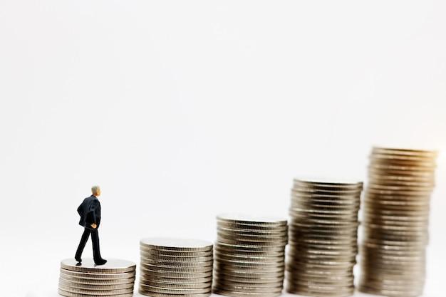Miniaturmenschen: geschäftsmann, der auf schritt des münzgeldes steht. konzept von finanzen und geld.