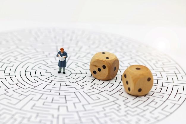 Miniaturmenschen: geschäftsmann, der in der mitte des labyrinths liest.