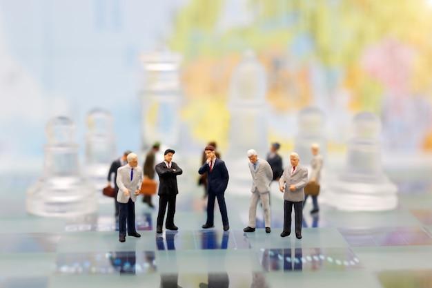 Miniaturmenschen, geschäftsmann mit glasschach, der auf schachbrett steht.
