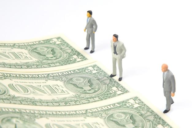 Miniaturmenschen. geschäftsmann steht in der nähe von dollargeld. investitionen und einkommen für die arbeit