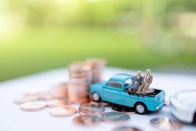 Miniaturmenschen: glückliche alte leute sitzen auf münzenstapel, alters- und lebensversicherungskonzept.