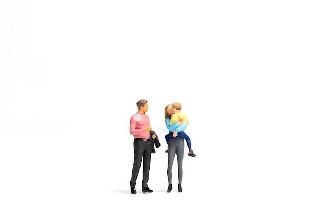 Miniaturmenschen glückliche familie, die auf weißem hintergrund steht und raum für text kopiert