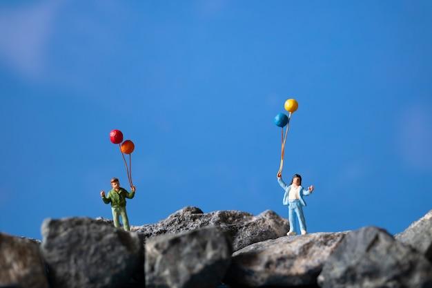 Miniaturmenschen, glückliche familie, die ballon auf dem felsen mit blauem himmel hält