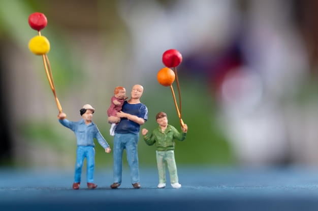Miniaturmenschen: glückliche familie, die ballon im park hält