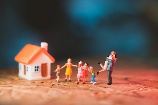 Miniaturmenschen, glückliche familie, die mit minihaus steht, das als familien- und eigentumskonzept verwendet