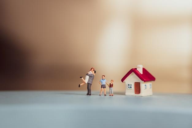 Miniaturmenschen, glückliche familie, die mit rotem haus steht, das als familien- und eigentumskonzept verwendet - weinlesefilter
