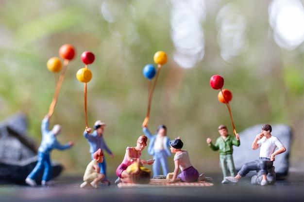 Miniaturmenschen: glückliche familie, die während eines picknicks in einem park auf der matte sitzt