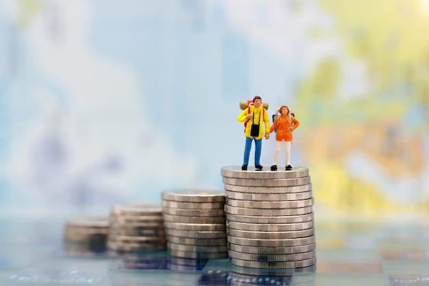 Miniaturmenschen: glückliches paar rucksacktourist, der auf münzstapel steht.
