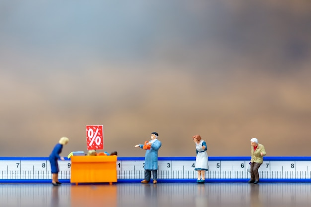 Miniaturmenschen halten abstand zum einkaufszentrum und zum öffentlichen bereich. soziales distanzierungskonzept.