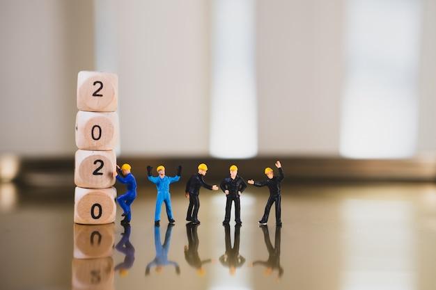 Miniaturmenschen, ingenieurteam stehend mit minihaus und holzblockjahr 2020 unter verwendung als immobilien- und industriekonzept