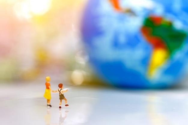 Miniaturmenschen, kinder mit bruder mit globus zu fuß zum ziel