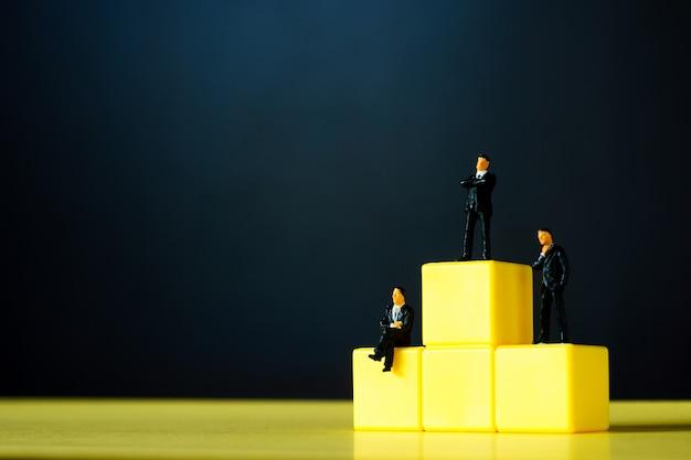 Miniaturmenschen: kleinunternehmerfiguren stehen auf gelbem podium mit schwarzer oberfläche