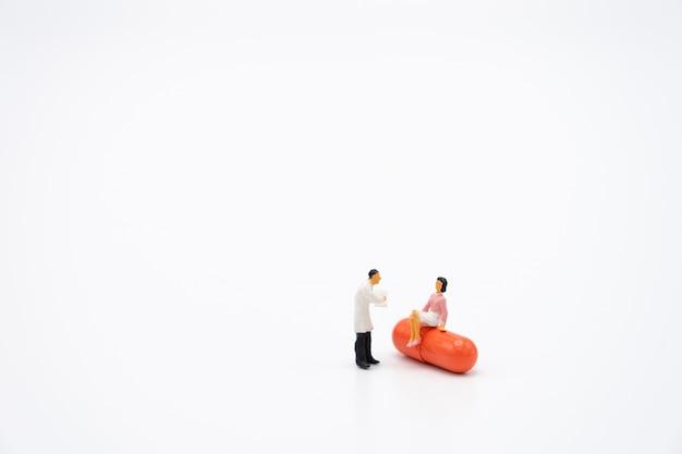 Miniaturmenschen konsultieren sie einen arzt, um nach gesundheitlichen problemen zu fragen. jährlicher gesundheitscheck oder arzt konsultieren.