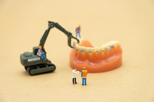 Miniaturmenschen konsultieren sie einen arzt, um nach gesundheitlichen problemen zu fragen.