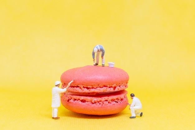 Miniaturmenschen: maler, die makronen färben