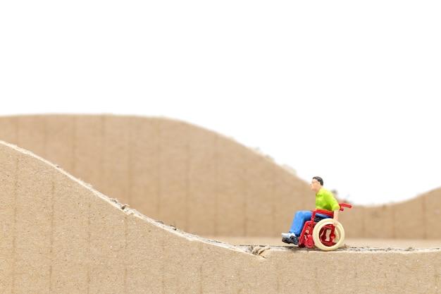 Miniaturmenschen mann im rollstuhl