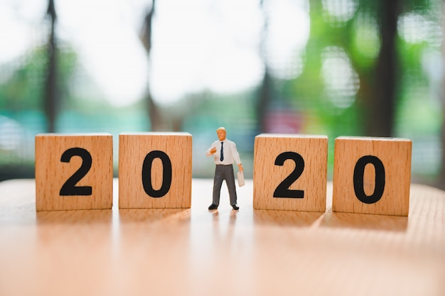 Miniaturmenschen, mann stehend mit holzblockjahr 2020 unter verwendung als geschäfts- und bildungskonzept