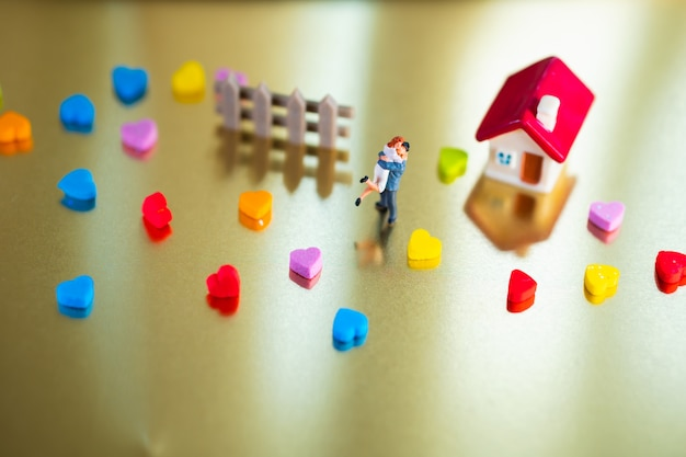 Miniaturmenschen, mann umarmen frau am minihaus, das als familien- und valentinstagkonzept verwendet