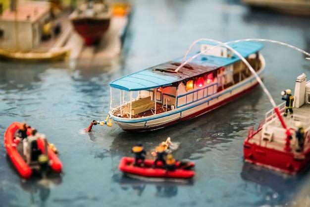 Miniaturmenschen. miniaturmodelle von feuerwehrleuten löschen ein feuer auf einem boot auf dem wasser. miniaturmodelle als hobby. modellbau.