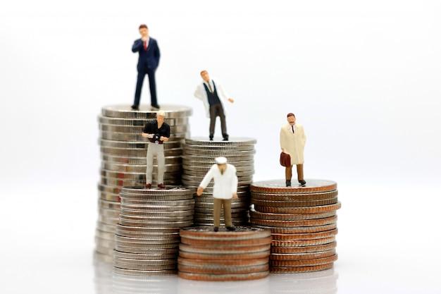 Miniaturmenschen mit verschiedenen berufen, die auf münzengeld stehen.