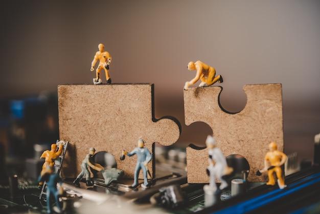 Miniaturmenschen oder kleine figurenarbeiter an puzzles zum verbinden. ideen zum aufbau eines geschäftsnetzwerkkonzepts.