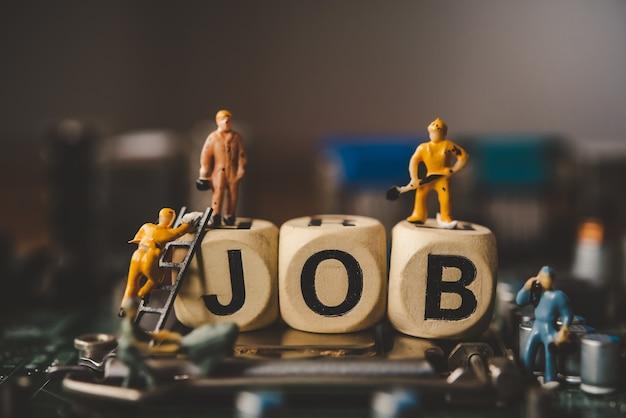 Miniaturmenschen oder kleinfigurenarbeiter auf holzblock mit dem wort
