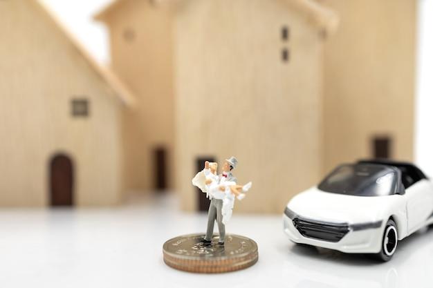 Miniaturmenschen: paar in brautkleidern stehen auf münzenstapel mit haus und auto. familienplanung und wohnkonzept.