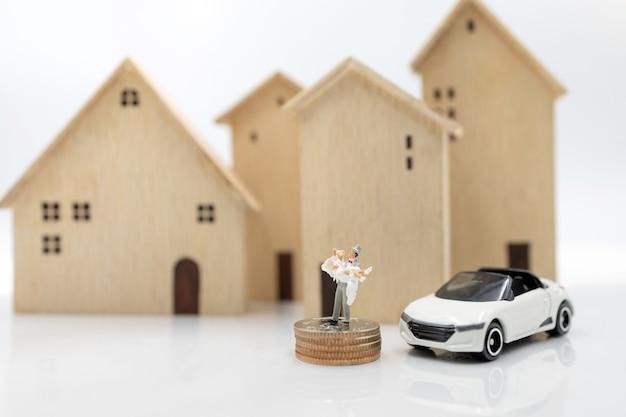 Miniaturmenschen: paare in brautkleidern stehen auf münzstapel mit haus und auto. familienplanung und wohnkonzept.