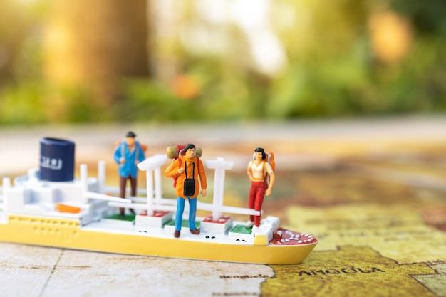 Miniaturmenschen: reisen mit einem rucksack, der auf vintage-weltkarte, reise- und sommerkonzept steht.