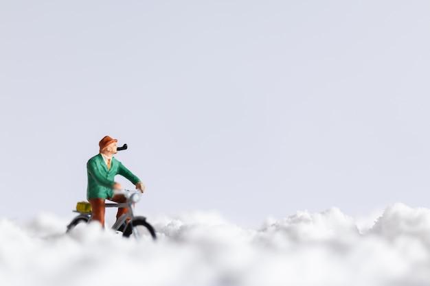 Miniaturmenschen: reisende, die auf schnee fahrrad fahren