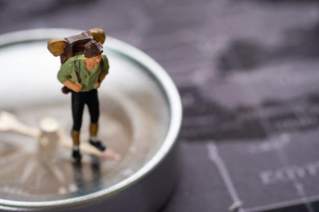 Miniaturmenschen: reisende mit rucksack, die auf dem kompass stehen, um die fahrtrichtung zu bestimmen.