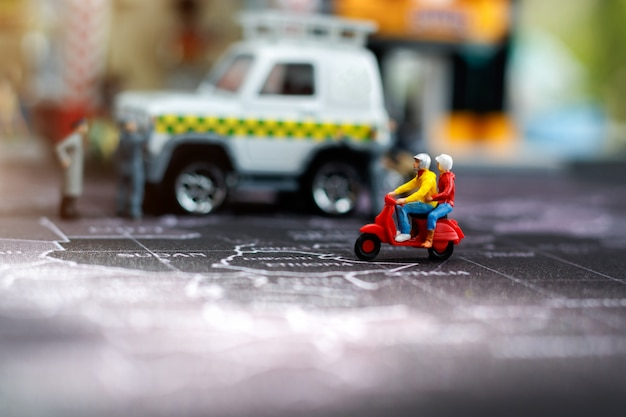 Miniaturmenschen: reisende paar fahren auf der motorradstadtstraße.