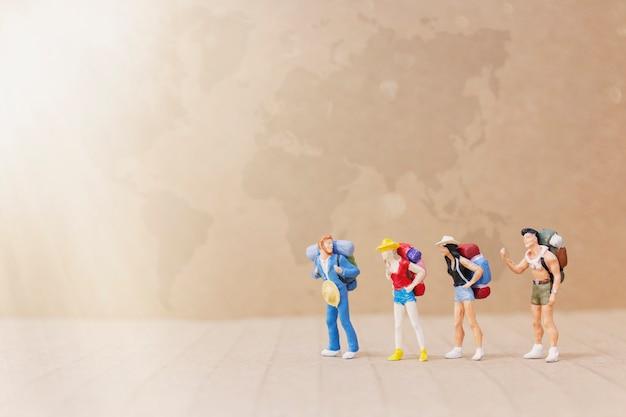 Miniaturmenschen: reisender mit dem rucksack, der auf die karte geht