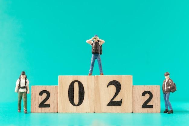Miniaturmenschen: rucksacktouristen und touristen, die auf holzblock nummer 2022 stehen, frohes neues jahr-konzept
