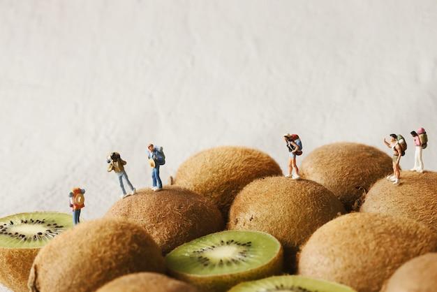 Miniaturmenschen-rucksacktouristengruppe, die auf kiwi-berg geht.