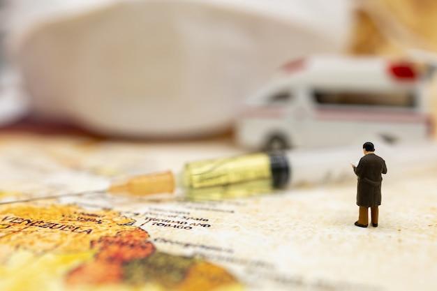 Miniaturmenschen stehen auf der weltkarte mit krankenwagen, medizinischer maske und spritze mit covid-19-impfstoff. impfstoff und medizinisches konzept für das gesundheitswesen.